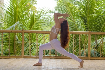 outdoors natural portrait of young beautiful and happy red hair woman doing yoga at tropical fitness studio practicing balance and concentration with jungle background in healthy lifestyle concept