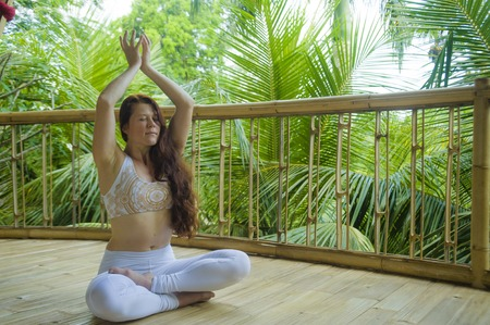 natural portrait of young attractive and happy relaxed woman sitting in lotus yoga position doing meditation and concentration outdoors at wooden hut in beautiful tropical jungle background