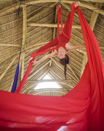 young attractive and happy athletic aerialist woman hanging from silk fabric doing aerial dancing workout training happy at beautiful wooden hut in artistic gymnastic balance exercise Imagens - 122506107