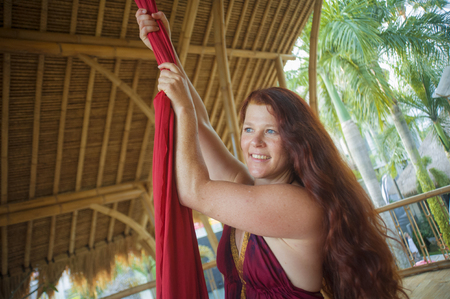 portrait of young happy and beautiful red hair woman at aerial dancing workshop learning aero dance holding silk fabric smiling cheerful in tropical wooden hut Stock fotó