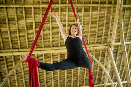 young attractive and happy athletic aerialist woman hanging from silk fabric doing aerial dancing workout training happy at beautiful wooden hut in artistic gymnastic balance exercise 版權商用圖片