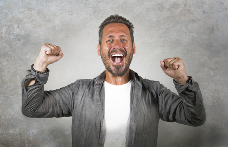 portrait of young happy and attractive Caucasian man gesturing with fist raising arms in victory and success sign smiling cheerful excited feeling strong emotion isolated on studio background