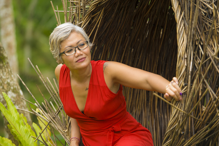 natural lifestyle portrait of attractive and happy middle aged 40s or 50s Asian tourist woman with grey hair and elegant red dress sitting outdoors at tropical jungle relaxed admiring beauty of nature 版權商用圖片 - 122796623