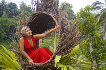 natural lifestyle portrait of attractive and happy middle aged 40s or 50s Asian tourist woman with grey hair and elegant red dress sitting outdoors at tropical jungle relaxed admiring beauty of nature