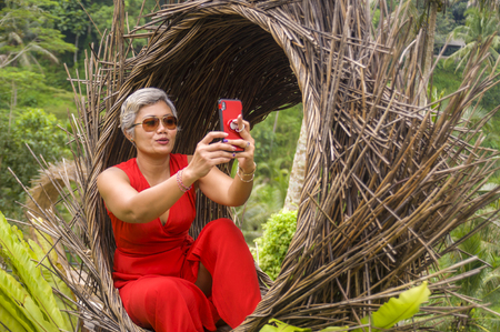 natural lifestyle portrait of attractive and happy middle aged 40s or 50s Asian woman with grey hair and stylish dress taking selfie photo with mobile phone outdoors at beautiful tropical jungle