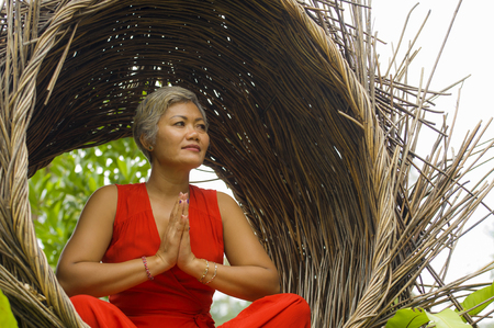 outdoors natural portrait of attractive and happy 40s or 50s middle aged Asian woman in classy and beautiful red dress practicing yoga relaxation and meditation in tropical jungle background 版權商用圖片 - 122796645