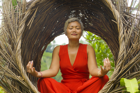 outdoors natural portrait of attractive and happy 40s or 50s middle aged Asian woman in classy and beautiful red dress practicing yoga relaxation and meditation in tropical jungle background 版權商用圖片 - 122796664