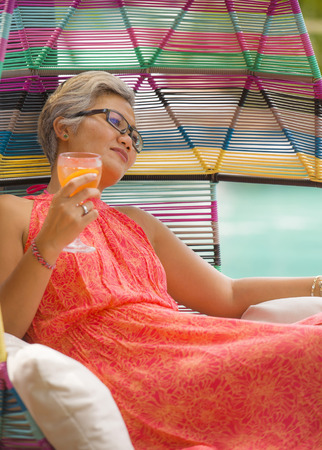 natural lifestyle portrait of attractive and happy 40s or 50s middle aged Asian woman with grey hair and stylish Summer dress enjoying drink at pool resort hammock relaxed in holidays travel concept