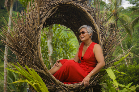 natural lifestyle portrait of attractive and happy middle aged 40s or 50s Asian tourist woman with grey hair and elegant red dress sitting outdoors at tropical jungle relaxed admiring beauty of nature 写真素材 - 122796687