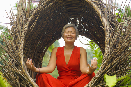 outdoors natural portrait of attractive and happy 40s or 50s middle aged Asian woman in classy and beautiful red dress practicing yoga relaxation and meditation in tropical jungle background