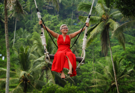 natural lifestyle portrait of attractive happy middle aged 40s - 50s Asian woman with grey hair and stylish red dress riding rainforest swing carefree swinging enjoying tropical jungle holidays