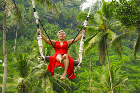 natural lifestyle portrait of attractive happy middle aged 40s - 50s Asian woman with grey hair and stylish red dress riding rainforest swing carefree swinging enjoying tropical jungle holidays Stock Photo