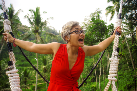 outdoors lifestyle portrait of attractive happy middle aged 40s or 50s Asian Indonesian woman with grey hair riding rainforest swing carefree swinging and enjoying tropical jungle adventure