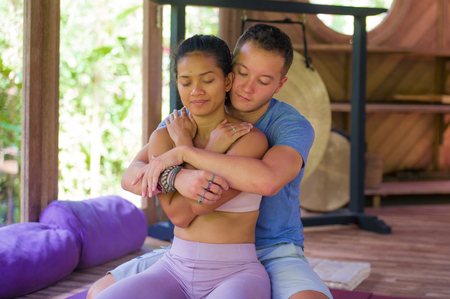 young beautiful and exotic Asian Balinese woman receiving body healing Thai massage by attractive Caucasian masseur man at traditional wellness spa garden in relaxation and beauty treatment