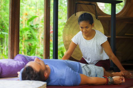 young beautiful and exotic Asian Balinese wellness therapist giving  body Thai massage to attractive Caucasian man in traditional garden spa in health care relaxation and harmony lifestyle concept