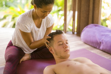 young beautiful and exotic Asian Balinese therapist woman giving traditional head and facial Thai massage to Caucasian man in harmony health care and wellness lifestyle at relaxing tropical spa 写真素材