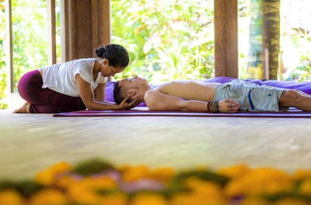 natural lifestyle portrait of young beautiful and exotic Asian Thai therapist woman giving traditional head and facial Balinese massage to Caucasian man at alternative medicine healing spa