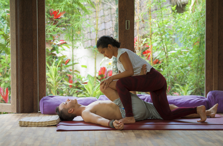 young beautiful and exotic Asian Indonesian therapist woman giving traditional Thai massage to man lying relaxed at tropical wellness spa in healthy natural lifestyle and body care Stock Photo