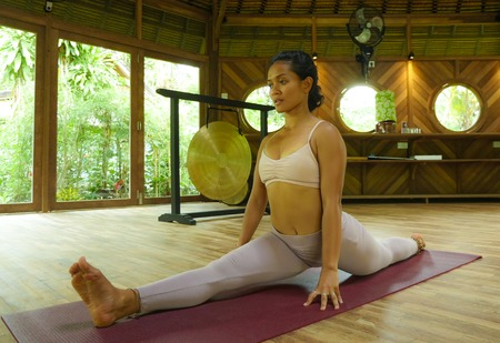 young attractive and healthy Asian Indonesian acrobat woman practicing acro yoga exercise in balance pose at traditional studio training concentrated in harmony and wellness lifestyle 写真素材