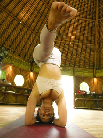 young attractive and healthy Asian Indonesian acrobat woman practicing acro yoga exercise in balance pose at traditional studio training concentrated in harmony and wellness lifestyle Stock Photo