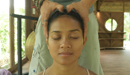 close up face portrait of young gorgeous and relaxed Asian Indonesian woman receiving traditional facial Thai massage with male hands working her head in wellness and natural health care
