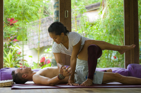 young beautiful and exotic Asian Indonesian therapist woman giving traditional Thai massage to man lying relaxed at tropical wellness spa in healthy natural lifestyle and body care 写真素材