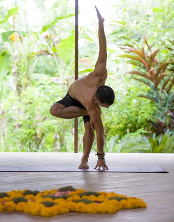 natural portrait of young attractive and fit acrobat man practicing yoga training balance exercise at beautiful tropical acroyoga and wellness studio in fitness and healthy lifestyle concept
