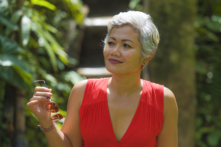 natural lifestyle portrait of beautiful and happy middle aged 40s or 50s Asian woman with grey hair in stylish red dress walking on green tropical jungle landscape enjoying adventure holidays trip