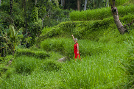 natural lifestyle portrait of beautiful and happy middle aged 40s or 50s Asian woman with grey hair in stylish red dress walking on green tropical forest landscape enjoying adventure holidays trip