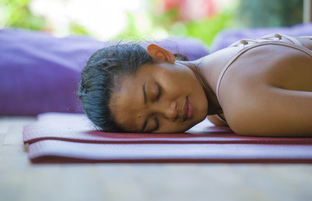 natural portrait of young beautiful and exotic Asian Indonesian woman lying relaxed on studio mat at yoga workshop with eyes close in meditation wellness and healthy lifestyle concept