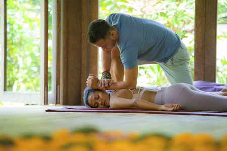 young beautiful and exotic Asian Balinese woman lying on studio mat receiving traditional Thai massage by masseur at tropical wellness spa garden in health care and body care concept 版權商用圖片