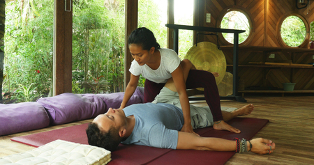 young beautiful and exotic Asian Indonesian therapist woman giving traditional Thai massage to man lying relaxed at tropical wellness spa in healthy natural lifestyle and body care Imagens