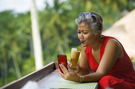 attractive and relaxed 40s or 50s Asian woman with grey hair and stylish red dress using social media on inernet mobile phone at beautiful tropical jungle resort drinking healthy juice