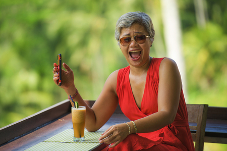 natural lifestyle portrait of attractive and relaxed 40s or 50s Asian woman with grey hair and stylish red dress using mobile phone laughing cheerful at beautiful tropical jungle resort 版權商用圖片