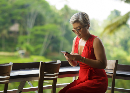 natural lifestyle portrait of attractive and relaxed 40s or 50s Asian woman with grey hair and stylish red dress using social media on inernet mobile phone at beautiful tropical jungle resort