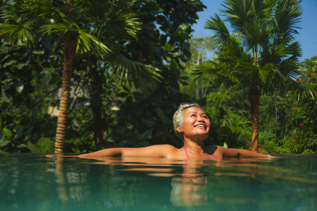 natural lifestyle portrait of attractive and happy middle aged Asian woman relaxed at tropical resort infinity swimming pool with jungle background enjoying relaxed in luxury holidays trip
