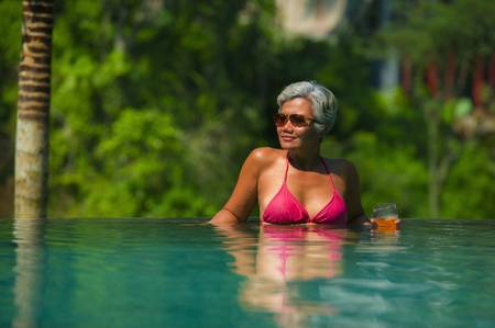 natural lifestyle portrait of attractive and happy middle aged Asian woman relaxed at tropical resort infinity simming pool with jungle background enjoying a drink relaxed in luxury holidays trip