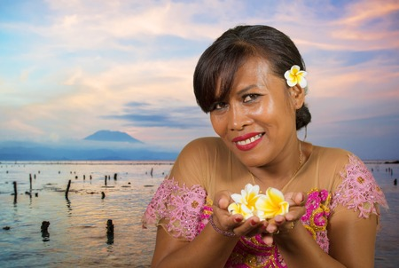 beautiful and happy middle aged Indonesian Balinese woman in traditional ceremony dress at tropical beach with Bali Agung volcano background in Hindu religion and holidays tourist destination 版權商用圖片