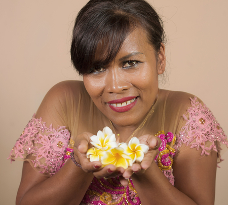 isolated portrait of beautiful and happy middle aged Indonesian Balinese woman in traditional ceremony dress smiling and holding flower offering in her hands in welcome to Bali Hindu religion 版權商用圖片