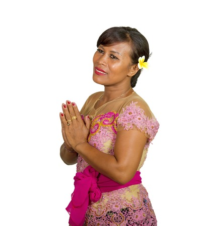 fresh portrait of beautiful and happy middle aged 40s Indonesian Balinese woman in traditional religious ceremony dress smiling cheerful on isolated background in welcome to Bali Hindu religion Stock Photo