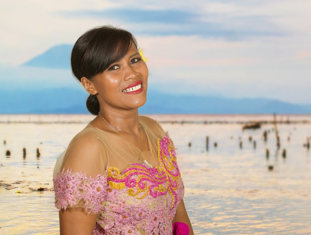 beautiful and happy middle aged Indonesian Balinese woman in traditional ceremony dress at tropical beach with Bali Agung volcano background in Hindu religion and holidays tourist destination Stockfoto
