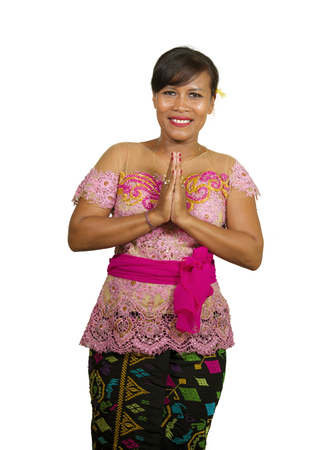 fresh portrait of beautiful and happy middle aged 40s Indonesian Balinese woman in traditional religious ceremony dress smiling cheerful on isolated background in welcome to Bali Hindu religion Imagens