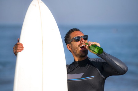 natural portrait of attractive and happy surfer man on his 40s carrying surf board after surfing morning at beautiful beach in wetsuit drinking beer bottle  enjoying Summer holiday and sport lifestyle
