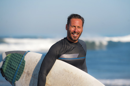 natural portrait of attractive and happy surfer man on his 40s carrying surf board after surfing morning at beautiful beach in wetsuit smiling enjoying Summer holiday and water sport lifestyle