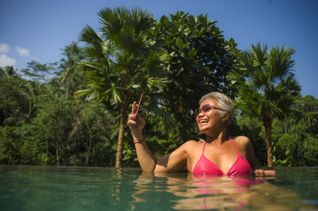 attractive and happy middle aged Asian Indonesian woman in bikini swimming at tropical luxury resort infinity pool taking selfie portrait with mobile phone enjoying Summer holiday destination
