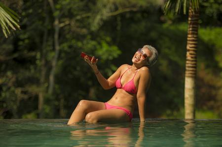 Attraktive und glückliche asiatische Indonesierin mittleren Alters im Bikini, die im Infinity-Pool des tropischen Luxusresorts schwimmt und ein Selfie-Porträt mit dem Handy macht, das den Sommerurlaub genießt
