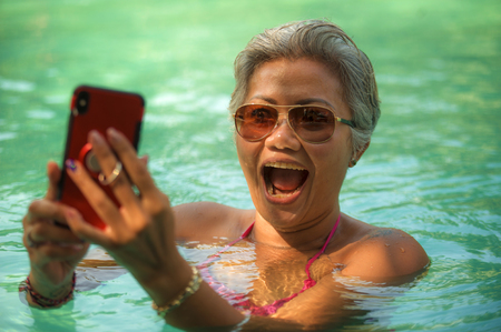 attractive and happy middle aged Asian Indonesian woman in bikini swimming at tropical luxury resort pool taking selfie portrait with mobile phone enjoying Summer holiday destination 写真素材