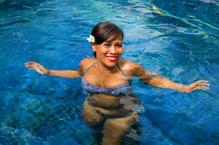 outdoors lifestyle portrait of middle aged 40s or 50s attractive and happy Asian Indonesian woman in biking enjoying holidays at Bali villa or tropical resort swimming pool smiling relaxed Stockfoto