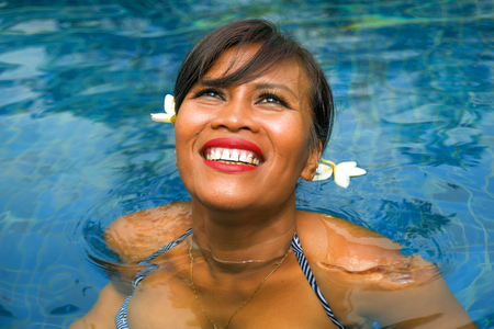 outdoors lifestyle portrait of middle aged 40s or 50s attractive and happy Asian Indonesian woman in biking enjoying holidays at Bali villa or tropical resort swimming pool smiling relaxed 写真素材