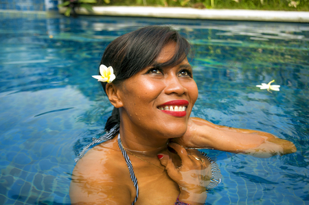 outdoors lifestyle portrait of middle aged 40s or 50s attractive and happy Asian Indonesian woman in biking enjoying holidays at Bali villa or tropical resort swimming pool smiling relaxed 免版税图像 - 123034661